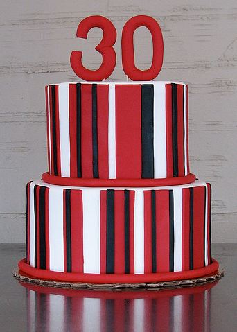 Two tier round birthday cake with red and black and white stripes